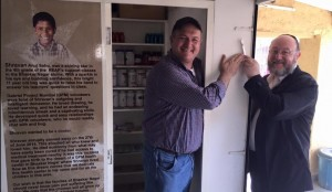 The Chief Rabbi affixes a mezuzah to the entrance of the Shravsn Medical Centre, an institution funded by The Gabriel Project, alongside the NGOs founder Jacob Sztokman